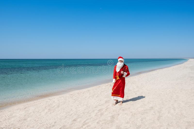 Santa Claus with a bag of gifts walking on the sandy beach royalty free stock photos
