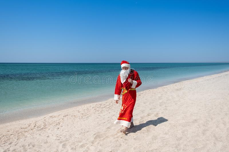 Santa Claus with a bag of gifts walking on the sandy beach. Turquoise water. Copy space for your text royalty free stock photos