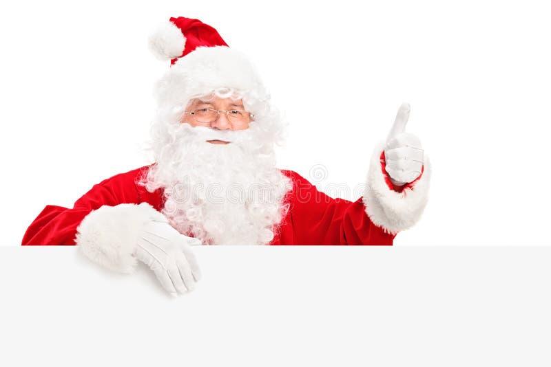 Santa Claus bak affischtavlan som ger upp en tum arkivfoton