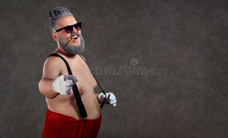 Santa Claus with a bare belly cigar in his teeth against. stock photography