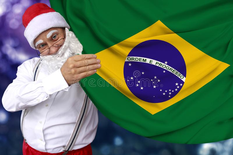 Santa Claus with a beard holds the beautiful colored national flag of the state of Brazil on fabric, concept of tourism, New Year stock photos