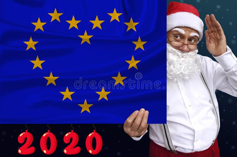 Santa Claus with a beard holds a beautiful photo of a stylized European Union flag with a festive date 2020, the concept of royalty free stock images