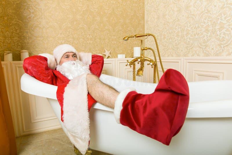 Santa Claus bebida divertida miente en un baño imágenes de archivo libres de regalías