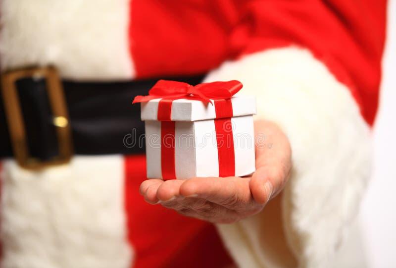 Santa Claus behandskade händer som rymmer gåvaasken arkivbild