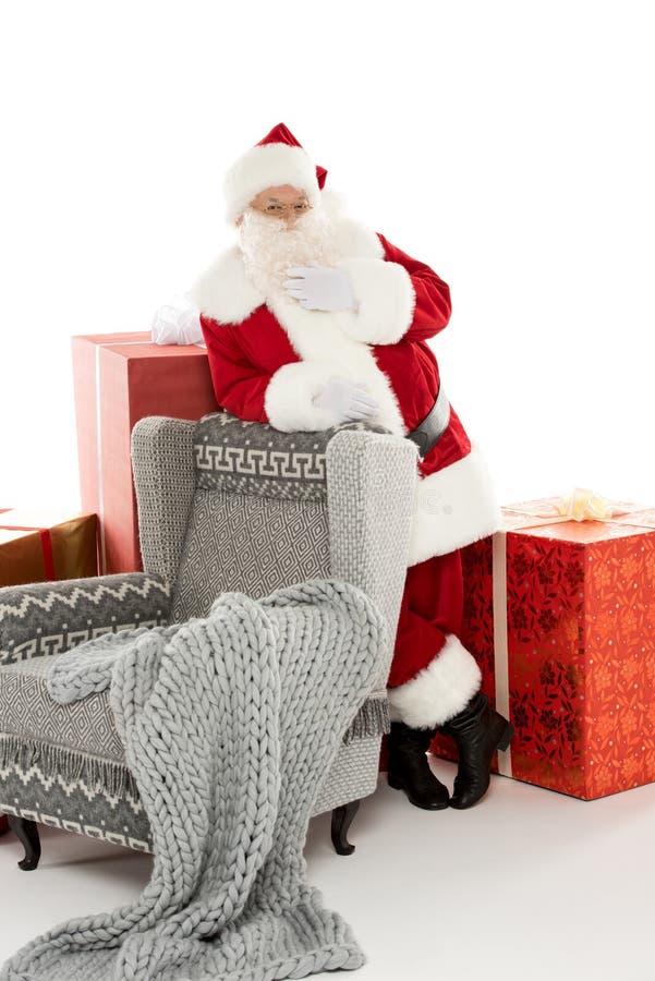 Santa Claus benägenhet på den gråa fåtöljen fotografering för bildbyråer