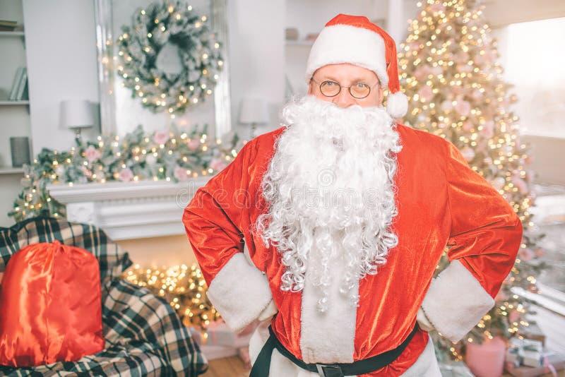 Santa Claus bevindt zich en stelt op camera Hij kijkt recht Zijn rode zak is op stoel De kerel kijkt ernstig royalty-vrije stock fotografie