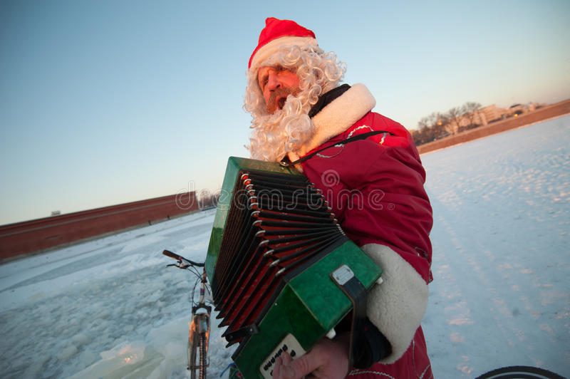 Santa Claus on a bike with an accordion. Saint-Petersburg, Russia - January 10, 2016: Santa Claus on the frozen river Neva in the center of the city against the royalty free stock images