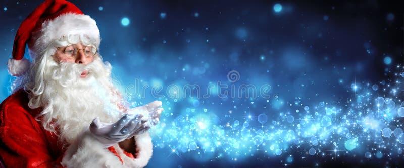 Santa Claus Blowing Magic Christmas Stars stock images