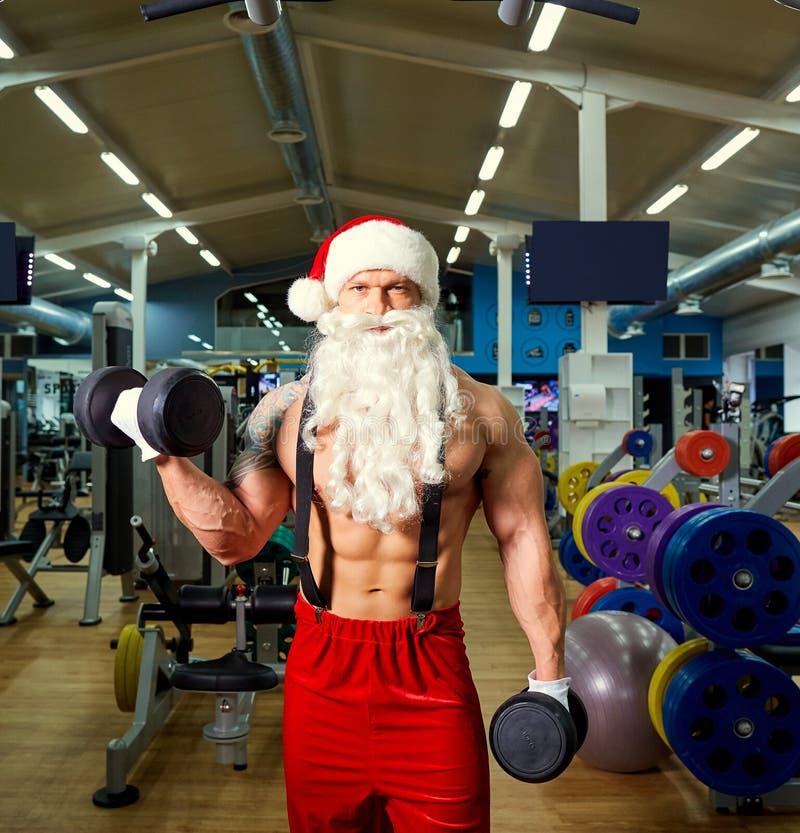 Santa Claus-bodybuilder in de gymnastiek bij Kerstmis stock foto