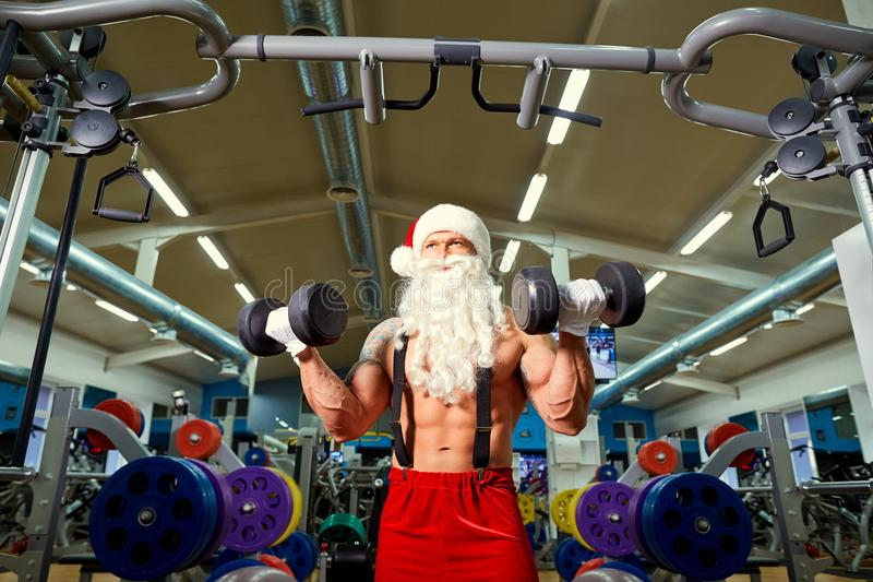 Santa Claus-bodybuilder met domoren in de gymnastiek bij Kerstmis stock foto