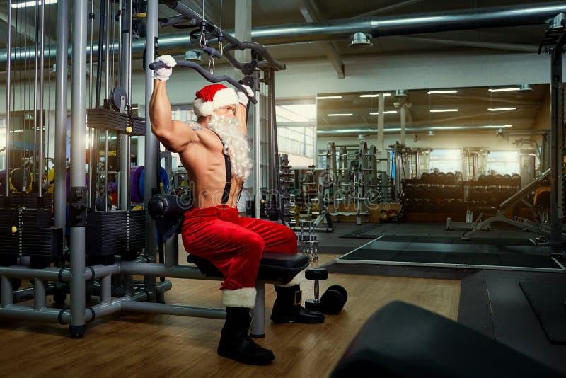 Santa Claus Bodybuilder utbildning på idrottshallen på juldagen royaltyfri bild