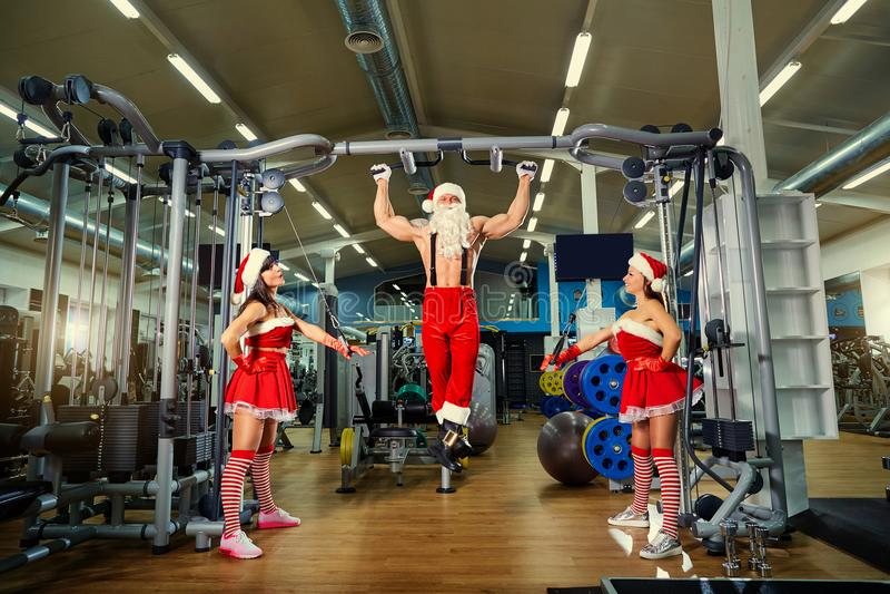 Santa Claus-bodybuildermeisjes in Kerstman` s kostuums bij een gymnastiek op CH stock foto's