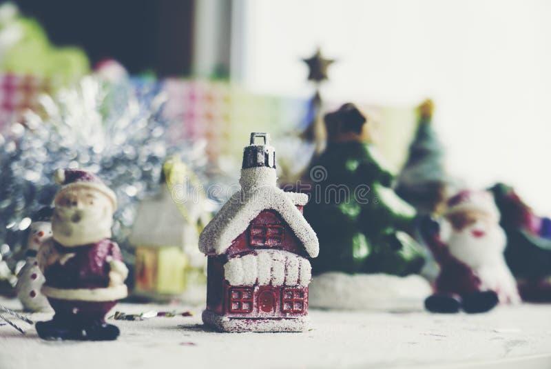 Santa Claus, boneco de neve, casas & estúdio modelo diminuto do pequeno trenó da neve disparado no fundo colorido para a família, imagens de stock