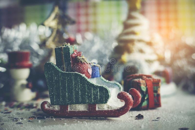 Santa Claus, boneco de neve, casas & estúdio modelo diminuto do pequeno trenó da neve disparado no fundo colorido para a família, fotografia de stock