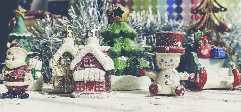 Santa Claus, boneco de neve, casas & estúdio modelo diminuto do pequeno trenó da neve disparado no fundo colorido para a família, imagens de stock royalty free