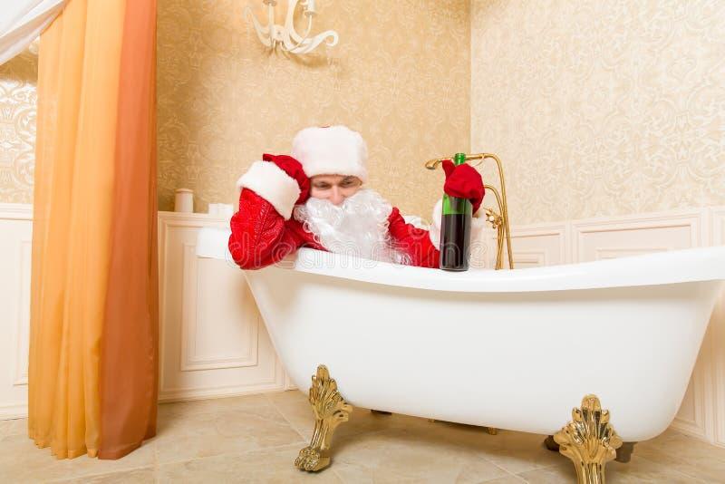 Santa Claus borracha con la botella que duerme en un baño imágenes de archivo libres de regalías
