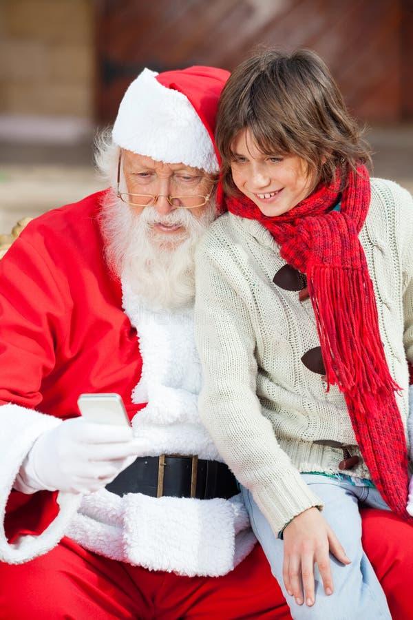 Santa Claus And Boy Using Smartphone stockfotos