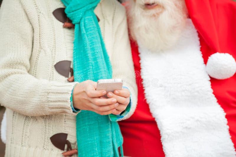 Santa Claus With Boy Using Smartphone lizenzfreie stockfotografie