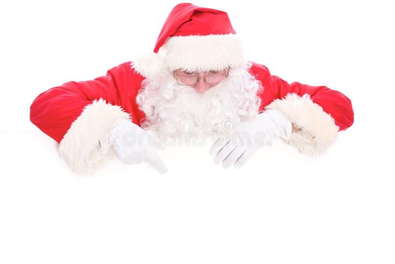 Santa Claus buena que mira hacia fuera de detrás la muestra en blanco aislada en el fondo blanco con el espacio de la copia fotos de archivo libres de regalías