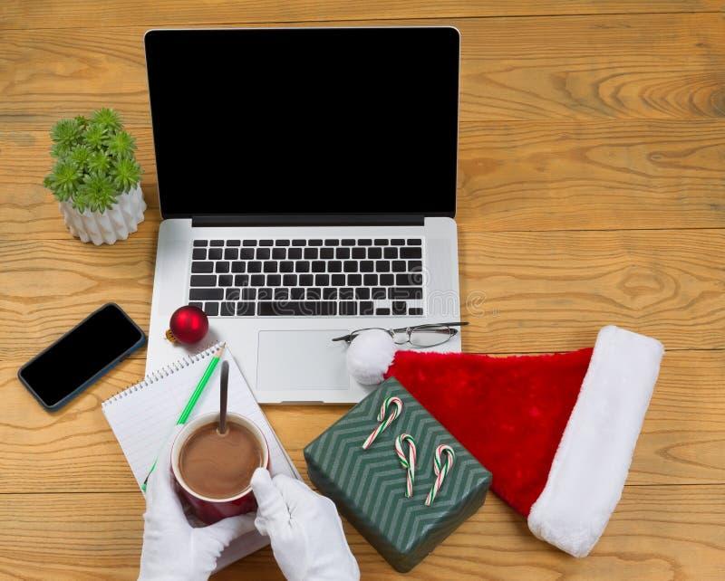 Santa Claus buvant du chocolat chaud tout en préparant pour travailler sur salut photo stock
