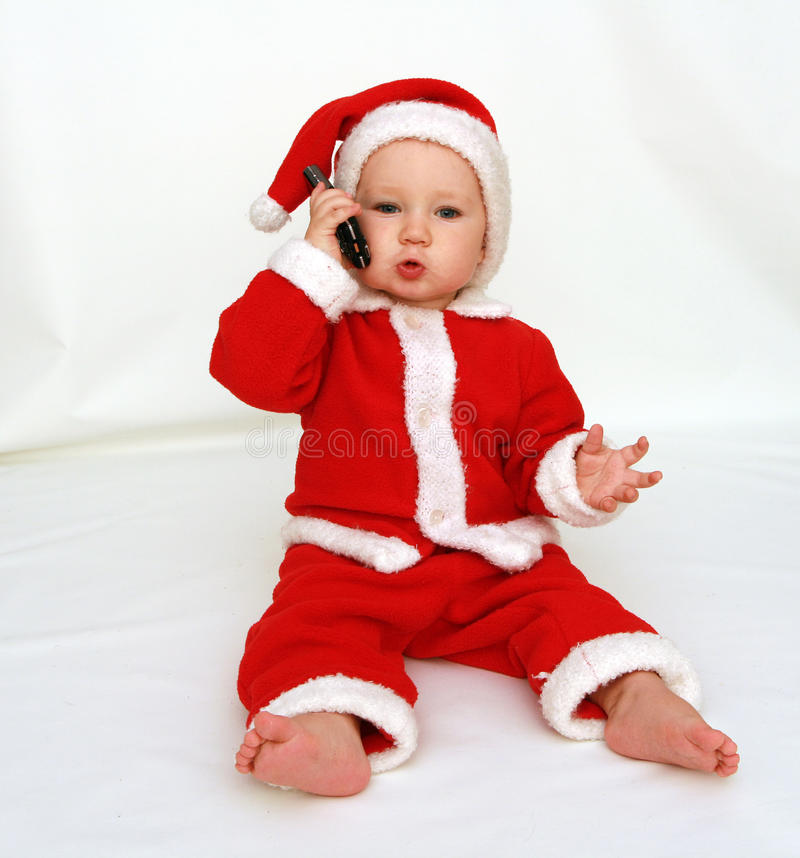 Santa Claus is calling. 12 months old baby boy dressed in santa claus costume with mobilphone in hand stock image