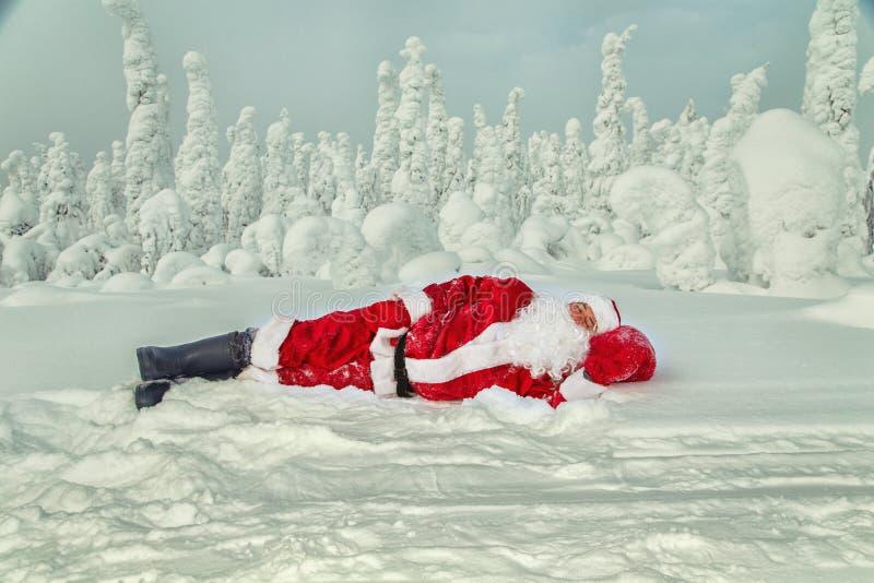 Santa Claus cansado caiu adormecido no ar livre foto de stock