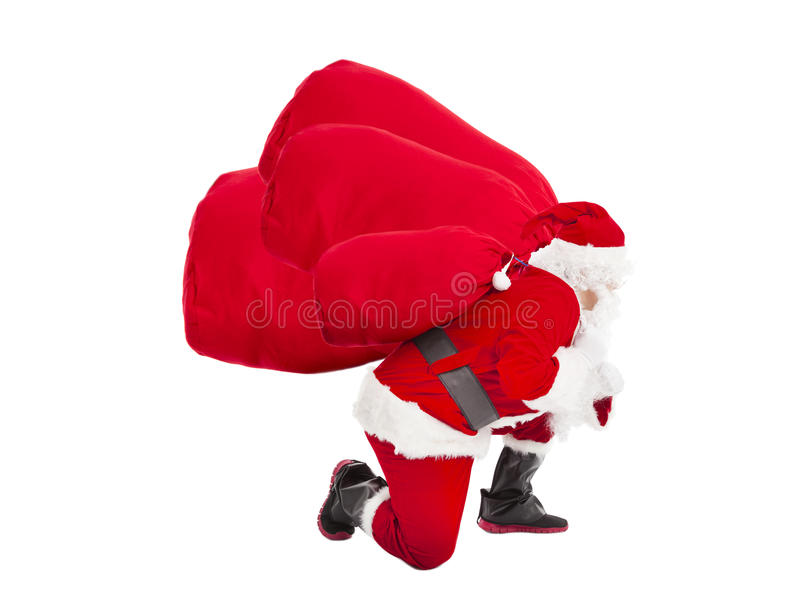 Santa claus carrying gift bags. Santa claus carrying heavy gift bags royalty free stock image