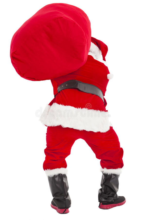 Santa claus carrying heavy gift bag. Isolated stock image