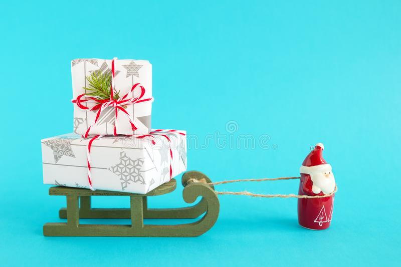 Santa Claus is carrying wooden sleigh with two gift boxes wrapped of white-gray paper, decorated of fir branch on blue background. Santa Claus is carrying green stock image