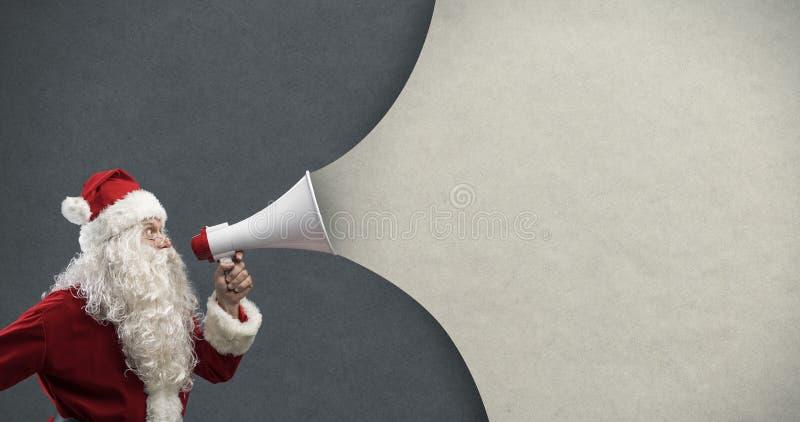 Santa Claus che annuncia un messaggio con un megafono fotografie stock