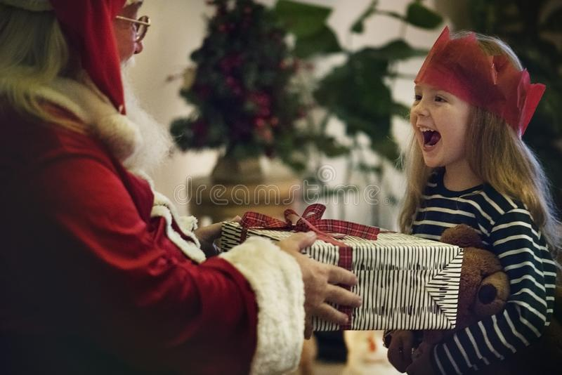 Santa Claus che cede un regalo ad una bambina immagini stock libere da diritti
