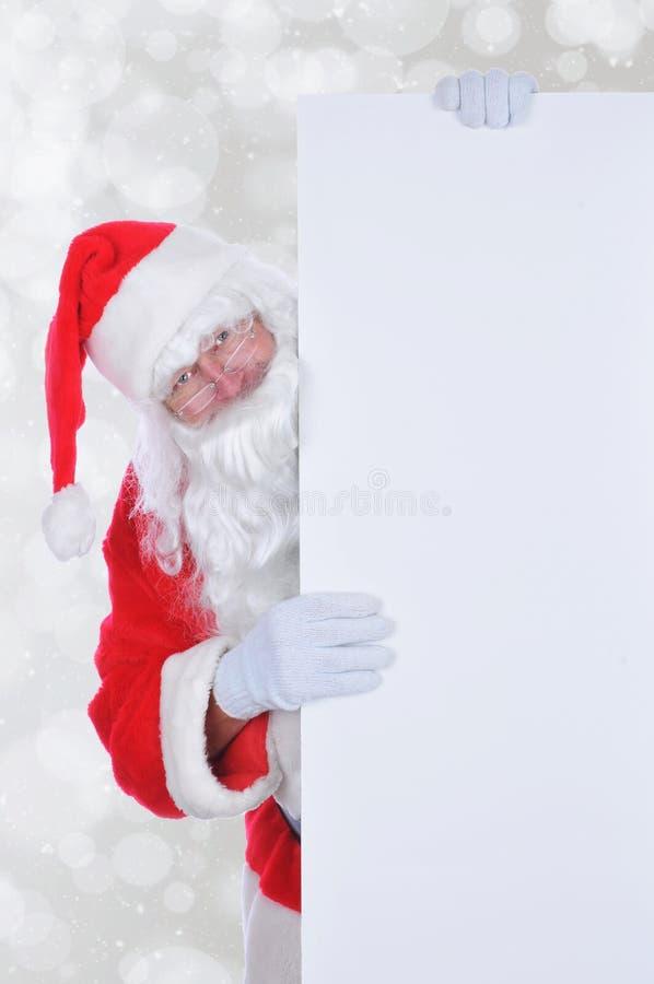 Santa Claus che dà una occhiata fuori da dietro un grande segno in bianco fotografie stock