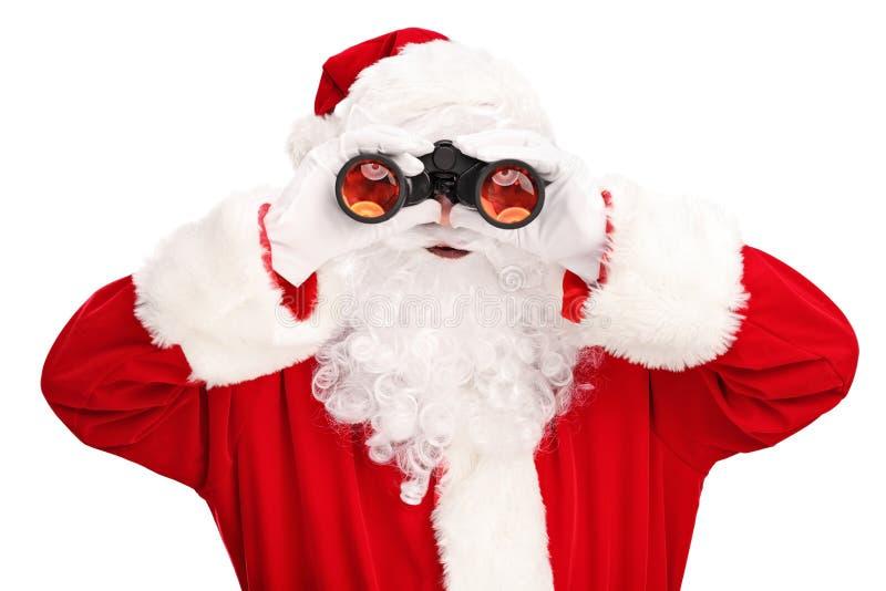 Santa Claus che guarda tramite il binocolo fotografie stock