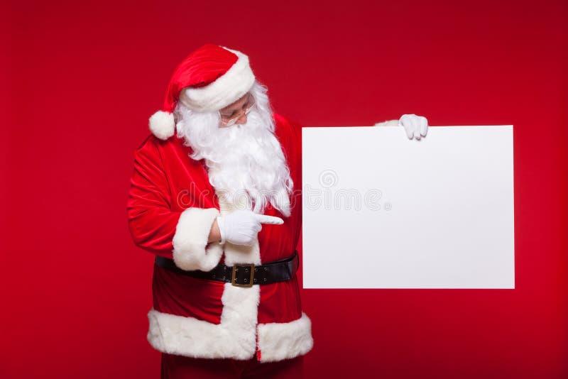 Santa Claus che indica nell'insegna in bianco della pubblicità isolata su fondo rosso con lo spazio della copia fotografia stock