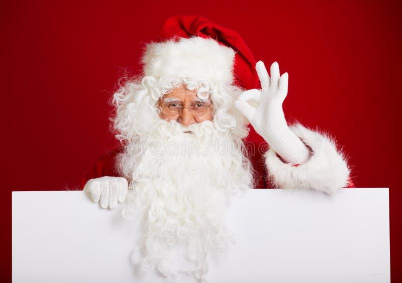 Santa Claus che indica nell'insegna in bianco della pubblicità isolata sulla r fotografia stock