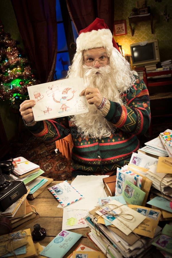 Santa Claus che mostra un disegno del bambino fotografie stock libere da diritti