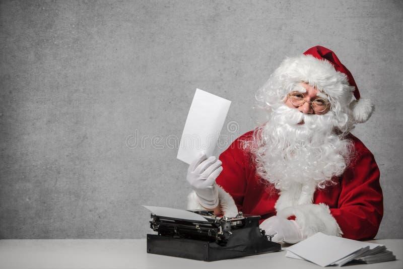 Santa Claus che risponde alla sua corrispondenza fotografia stock libera da diritti