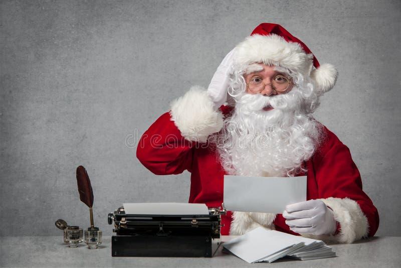 Santa Claus che risponde alla sua corrispondenza fotografia stock