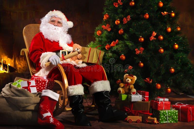 Santa Claus che si siede davanti al camino immagini stock libere da diritti