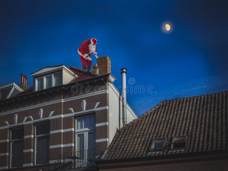 Santa Claus che si siede sul tetto della casa e mette presen immagini stock