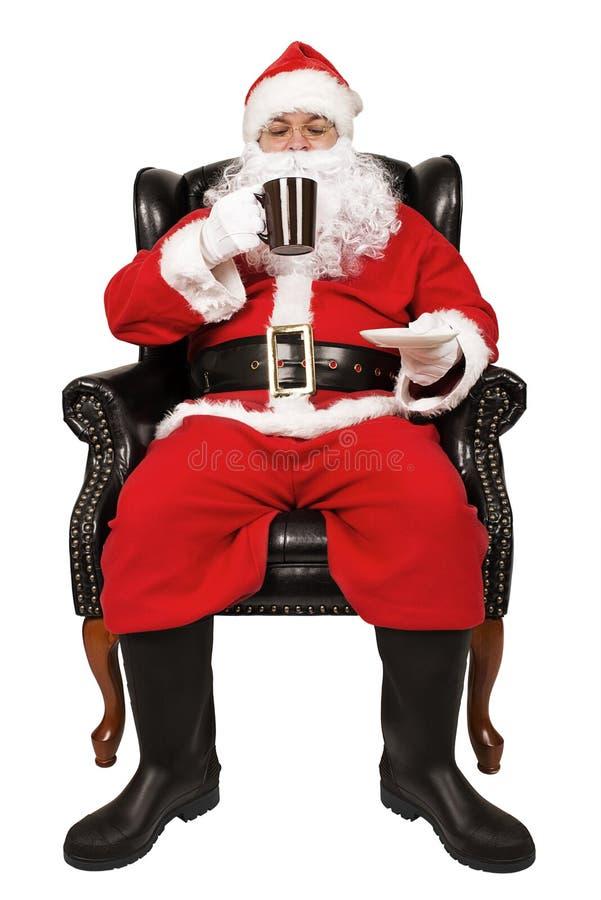 Santa Claus che si siede in una sedia sta bevendo una cioccolata calda immagine stock