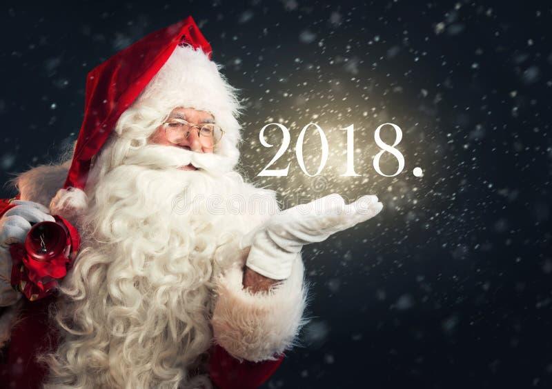 Santa Claus che soffia neve magica della sua mano, tenente un anno 2018 fotografia stock libera da diritti
