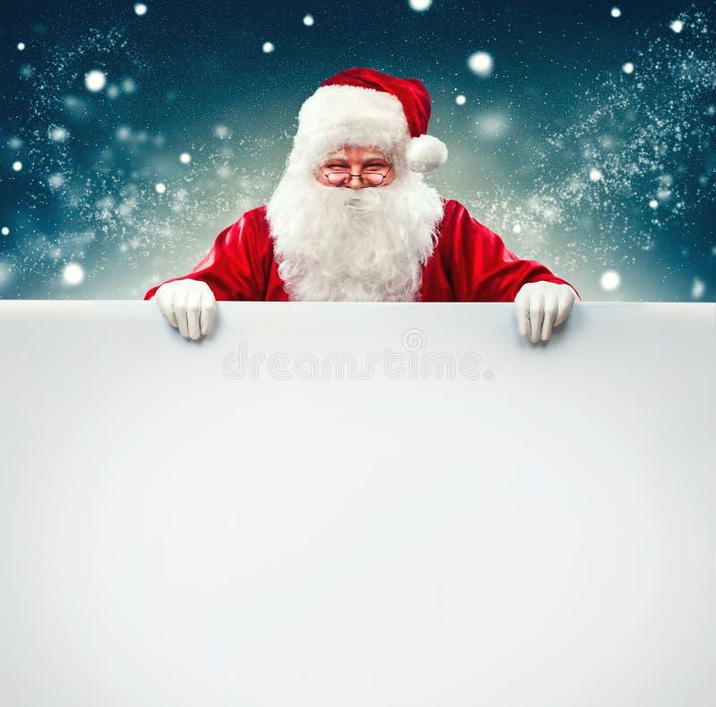 Santa Claus che tiene l'insegna in bianco della pubblicità immagine stock