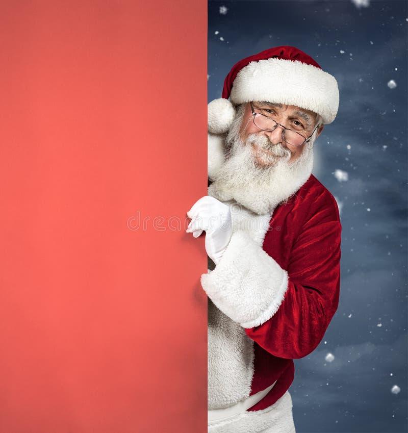 Santa Claus che tiene segno in bianco rosso, pubblicità di Natale immagine stock libera da diritti