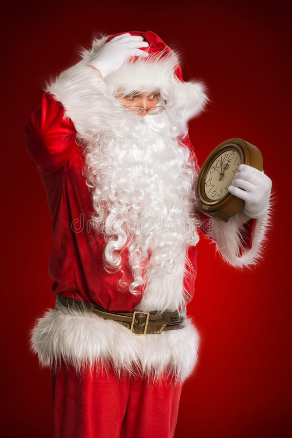 Santa Claus che tiene un orologio immagini stock