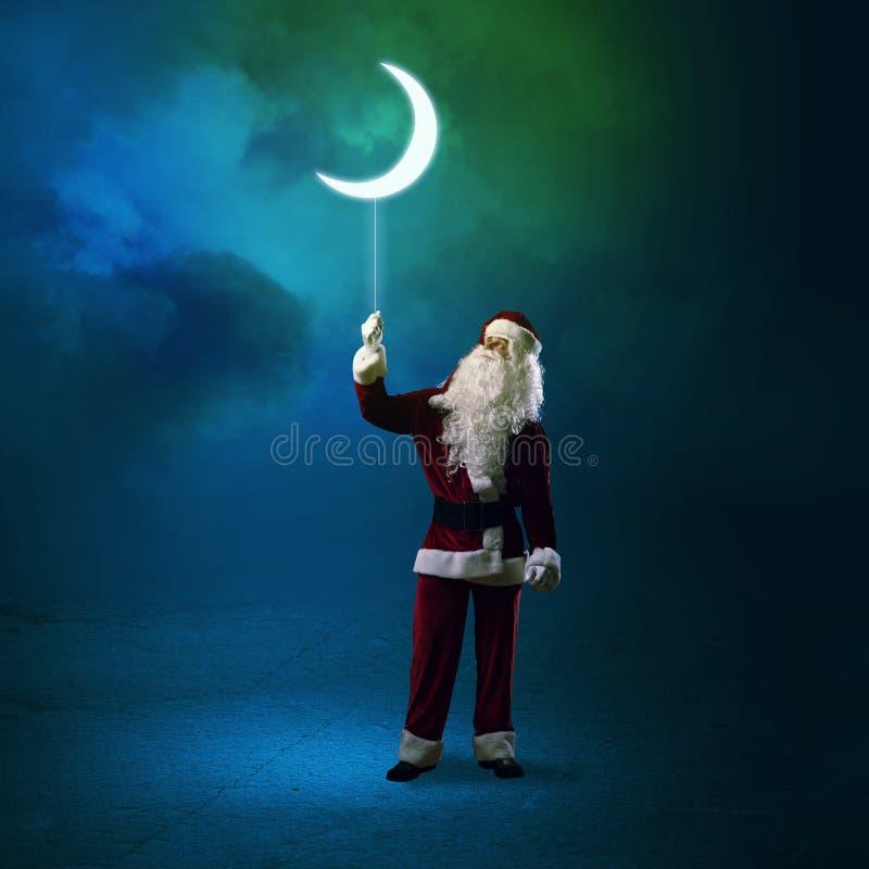 Santa Claus che tiene una luna brillante immagini stock libere da diritti