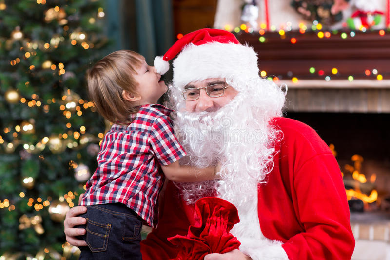 Santa Claus and child with presents at fireplace. Kid and father in Santa costume and beard stock image