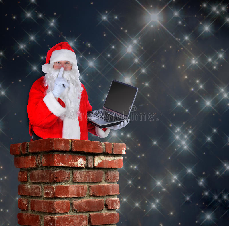 Santa Claus in Chimney. Santa Claus partially inside a chimney with a laptop and making the shh sign with a finger to his lips on a starry night background royalty free stock photography