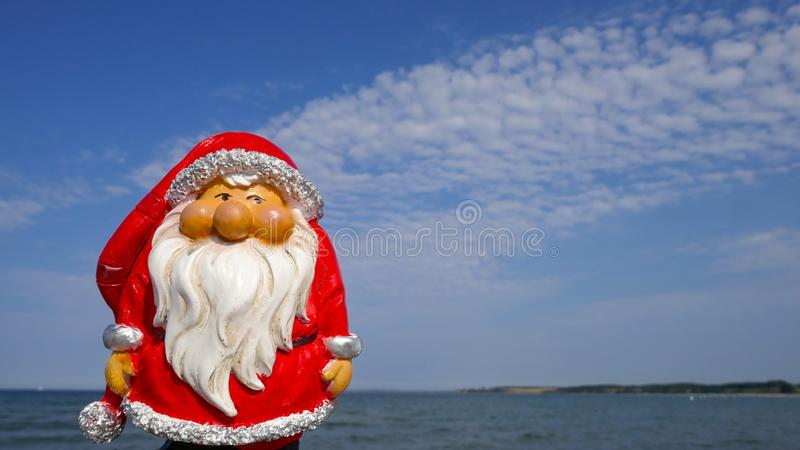 Santa Claus.Christmas by the sea. Little garden gnome in Santa Claus costume goes on vacation in the tropics royalty free stock photography