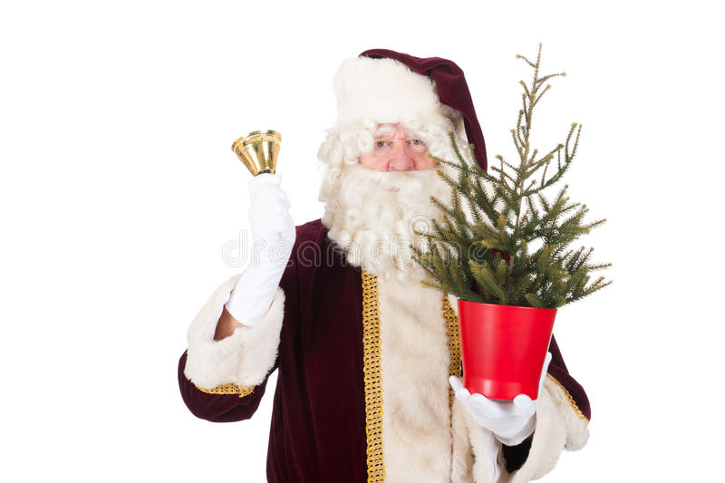 Santa Claus with Christmas tree. And copper bell isolated over white background royalty free stock photography